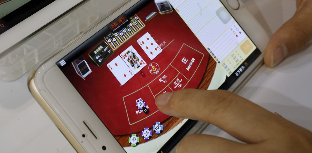 An attendant demonstrates an online baccarat game on a smartphone at the Global Gaming Expo Asia in Macau